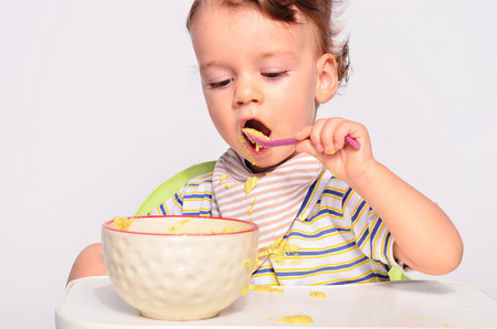 toddler boy: Baby eating food with a spoon, toddler eating messy and getting dirty, infant having oatmeal as breakfast