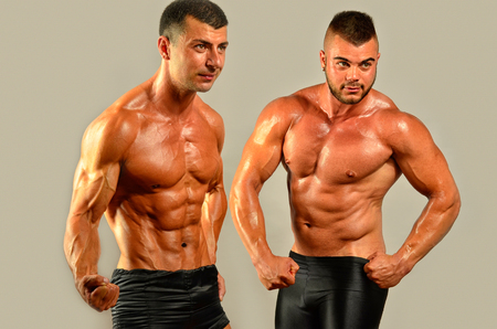 male body: Fit body versus fat body, flexing muscles. Two men showing their biceps,abs, chest and shoulders in a contest Stock Photo