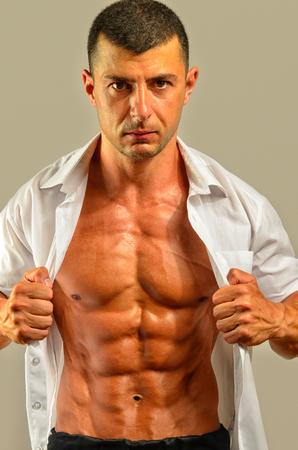 seins nus: Gros plan sur abdos parfaits. Forte bodybuilder Topless avec six pack, entraîneur personnel vêtu d'une chemise blanche fléchissant ses muscles