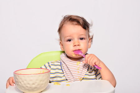 Baby eating food with a spoon, toddler eating messy and getting dirty, infant having oatmeal as breakfast