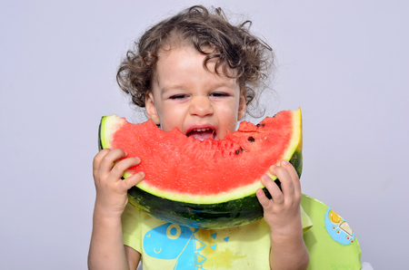 Toddler eating a slice of a sweet delicious watermelon. Hungry kid bitting from a piece of melon and getting messy