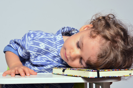 Toddler learning how to write and read. Small kid having fun preparing for school but too tired after a lesson, he went to sleep
