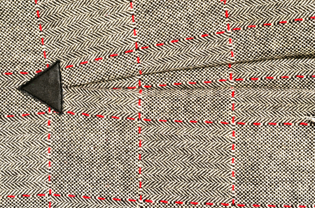 Wool fabric with red sewing and a leather triangle. Tartan design as background. Checked fabric.