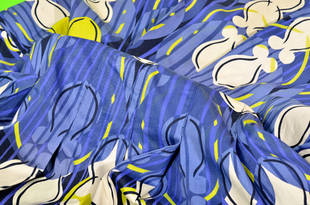 Blue with stripes folded fabric with white yellow print on blue background.