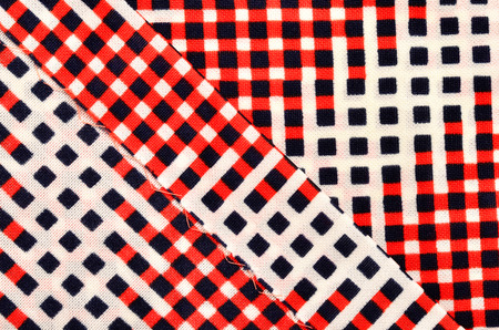 Red, white and blue squares print as background on fabric. Example of a stitched seam.