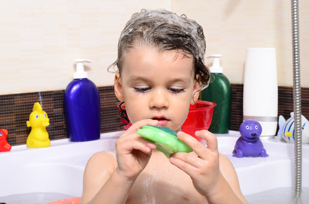 Beautiful toddler taking a bath in a bathtub with bubbles. Cute kid washing his hair with shampoo in the shower and splashing water everywhere. Boy playing with toys in the tub 写真素材