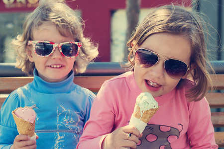 aviators: Two little girls sisters eating ice cream. Stock Photo