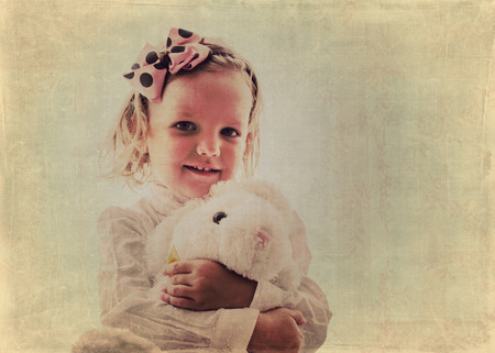 blurring: Art photo. Portrait of beautiful little girl in vintage style. The image is tinted, blurring and selective focus. Stock Photo