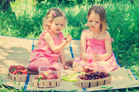 children clothing: Small cute funny girls sisters at the picnic. Selective focus. Stock Photo