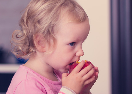 2 years: Funny little girl (2 years) eat a peach. Selective focus.