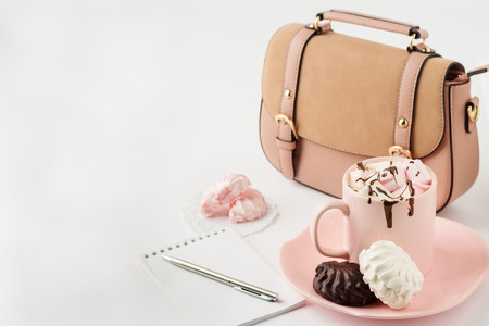 Warme chocolademelk met marshmallows, notitieblok en vrouwen handtas op een witte achtergrond. Selectieve aandacht.