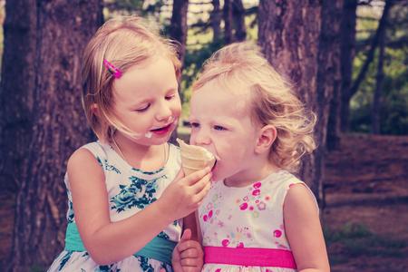 ni�as peque�as: Bastante ni�as (hermanas) helado de comer en el verano del parque. La imagen se ti�e.