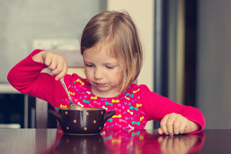 Beautiful little girl eating soup. The image is tinted.