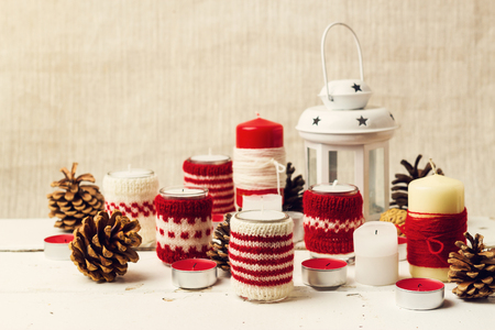 Christmas handmade. Christmas candles in the candle holders knitted. Selective focus. Reklamní fotografie