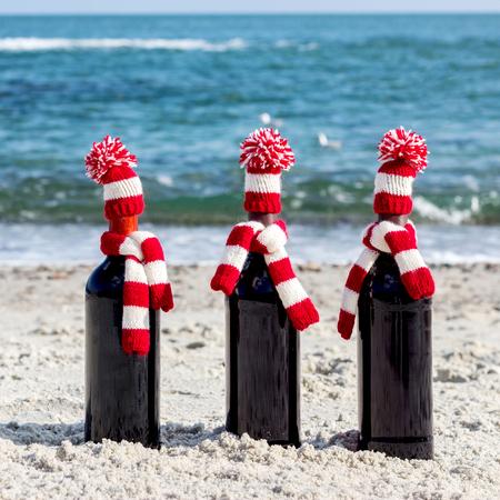 botella: Regalos de Navidad. Tres botellas de vino en sombreros y bufandas de punto en la playa. enfoque selectivo.