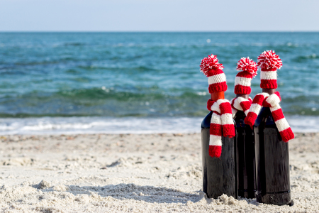 stria: Christmas gifts. Three bottles of wine in knitted  hats and scarves on the beach. Selective focus.