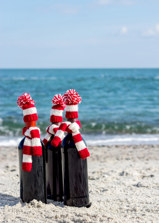 stria: Christmas gifts. Three bottles of wine in knitted hats and scarves on the beach. Selective focus. Stock Photo