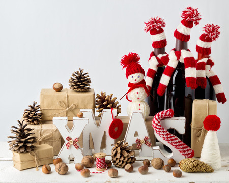 Vintage stile. Christmas card. Christmas decorations - letters XMAS, gifts, knitwear, nuts and bottles of wine in knitted hats. Reklamní fotografie