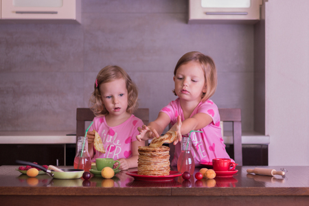 pancake week: Pancake week. Little girls (sisters) eat pancakes. Selective focus.