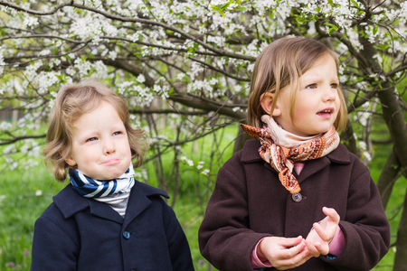 3 4 years: Cute little girls (sisters 3 and 4 years old) near flowering trees.