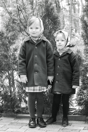 topcoat: Photo in retro style. Cute little girls (sisters 3 and 4 years) in the tissues. Selective focus.