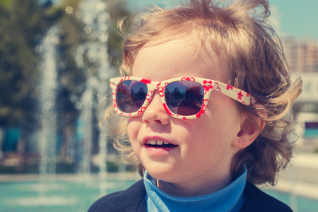 aviators: Beautiful little girl in sunglasses. The image is tinted.