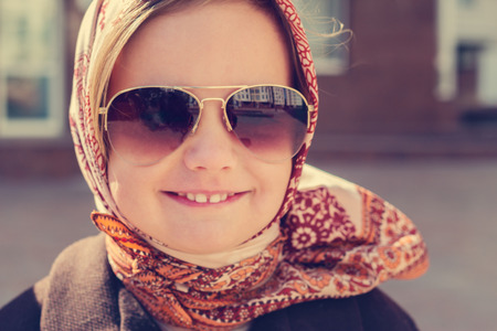 aviators: Beautiful little girl in a headscarf and sunglasses. The image is tinted.