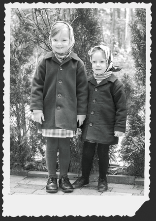 3 4 years: Photo in retro style. Cute little girls (sisters 3 and 4 years) in the tissues. Selective focus.