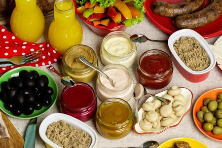 carnes y verduras: Mesa para una comida campestre del verano - verduras y champiñones, aceitunas, carnes, embutidos y patés, una variedad de salsas. Pan y jugo. enfoque selectivo. Foto de archivo