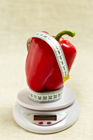 regimen: Concept of diet, health. Red sweet bell pepper with a meter on the white balance. Selective focus.