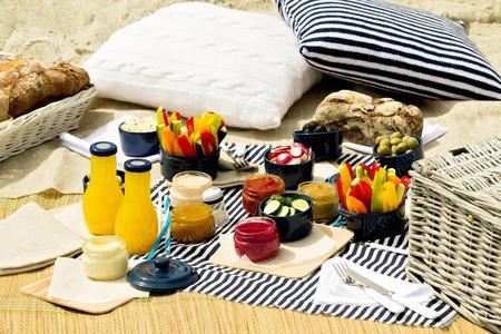 夏のビーチでピクニック。ストライプ テーブル クロスやニット枕のソースと野菜青のピクニック用品を提供します。選択と集中。