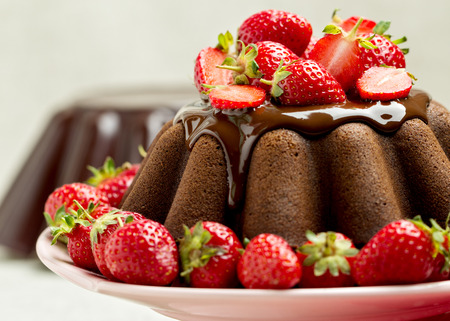 summer pudding: Chocolate cake. Decorating with chocolate icing and strawberries. Selective focus.
