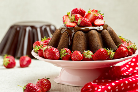 cake decorating: Chocolate cake. Decorating with chocolate icing and strawberries. Selective focus.