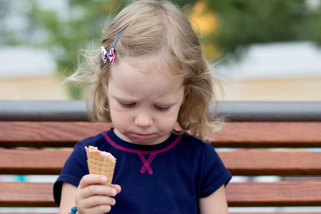 Funny little girl (3 years) eat ice cream. Selective focus. Stock Photo