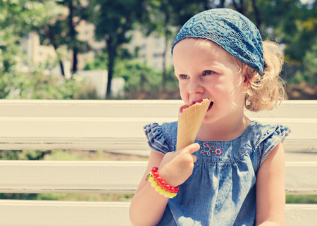 droll: Funny little girl (3 years) eat ice cream. Selective focus. Stock Photo