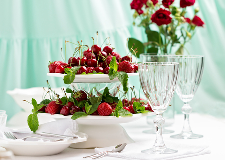 Summer. Table setting. Berries - strawberries and cherries at a stand in the center of the table. Selective focus.