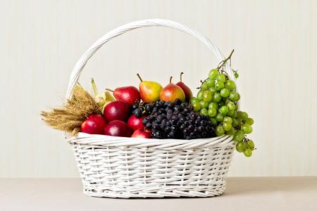 Weißer Korb mit Trauben, Äpfel und Birnen.