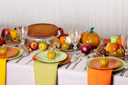 Thanksgiving dinner. Seasonal table setting with autumn leaves, candles and pumpkins.