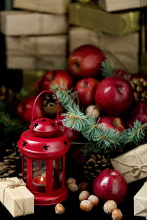 Christmas and New year. Apples with pine cones and nuts in a basket with fir branches. Gifts and candles.
