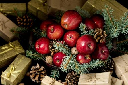 Kerstmis en Nieuwjaar. Appelen met denneappels en noten in een mand met spartakken. Geschenken en kaarsen.