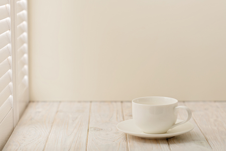 Cup on bright wooden background near a window with shutters. Imagens