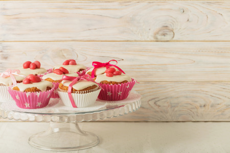 yarrow: Cupcakes with white icing decorated with pink candy and ribbons. Selective focus.