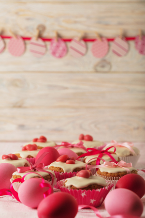 yarrow: Easter cupcakes with white icing decorated with pink candy and ribbons. Selective focus.