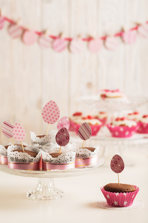 Easter cupcakes decorated with pink candy, paper eggs and ribbons. Selective focus.