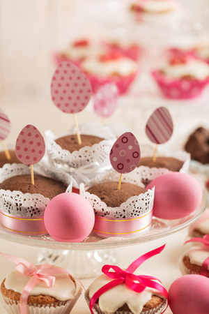 yarrow: Easter cupcakes decorated with pink candy, paper eggs and ribbons. Selective focus.