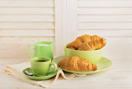 Coffee with milk and croissants on a light wooden background. Selective focus. Stock Photo