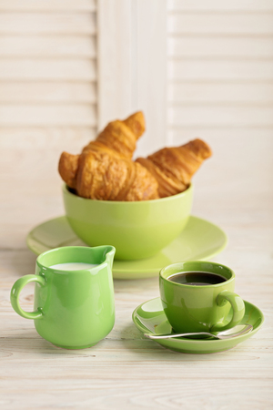 electronic book: Coffee with milk and croissants on a light wooden background. Selective focus. Stock Photo