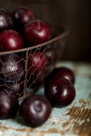 Ripe plums in a basket on a wooden background. Macro photo. Selective focus.