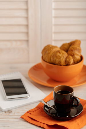 electronic book: Coffee with croissants, smartphone and a notepad. Selective focus. Stock Photo