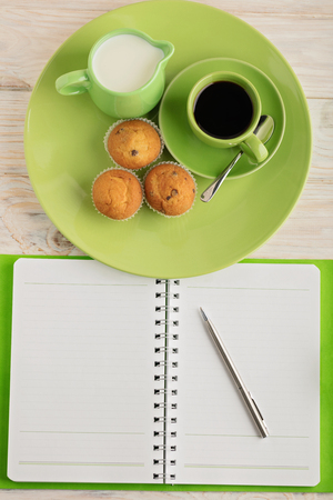 Coffee with milk, muffins and notepad on wooden background. Selective focus. Stock Photo